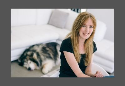 Image shows Rachel Amphlett posed in a studio laughing at the camera while the photographer's dog is sleeping on the floor behind her with its tongue out
