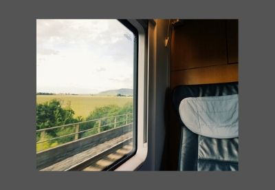 Image shows a seat on a train carriage beside a window with English countryside passing outside