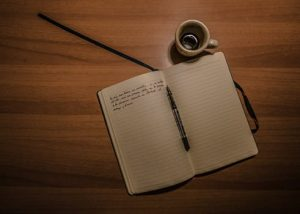Open notebook with writing and a coffee cup