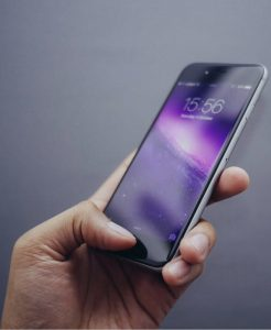 Person using iPhone with purple background vertical