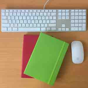 Notebooks and Apple keyboard on desk