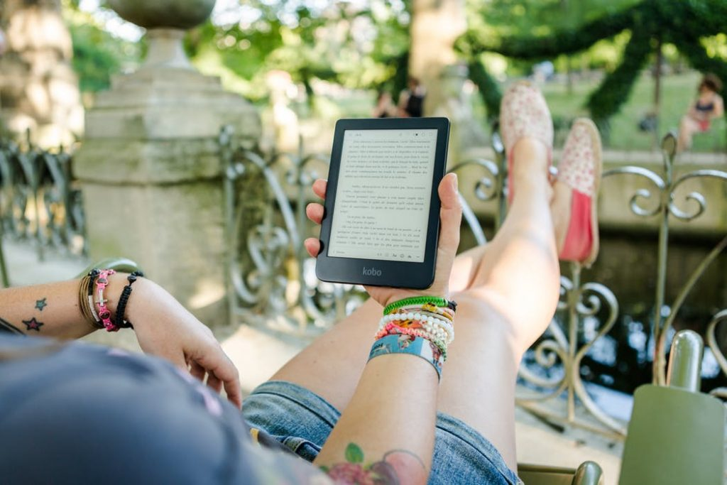 Woman reading a Kobo eReader on holiday feature image for blog