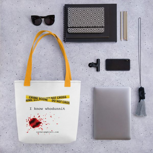 Image shows tote bag with yellow strap and yellow crime scene tape with the words I Know Whodunnit underneath and blood spatter