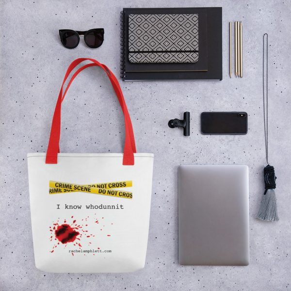 Image shows tote bag with red strap and yellow crime scene tape with the words I Know Whodunnit underneath and blood spatter