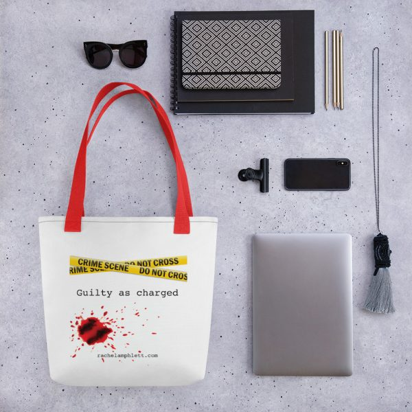 Image shows tote bag with red strap and yellow crime scene tape with the words Guilty as Charged underneath and blood spatter