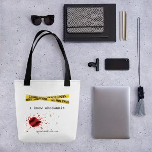 Image shows tote bag with black strap and yellow crime scene tape with the words I Know Whodunnit underneath and blood spatter
