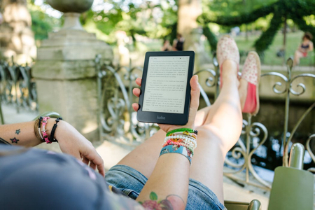 Image shows a woman reading a Kobo eReader on holiday 450x300