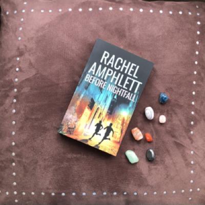 Before Nightfall book resting on a brown velvet background