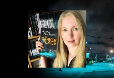 Rachel Amphlett holding a copy of A Darker Place next to a bookshelf displaying her books